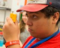 Joshua Reveles, 17, of Dallas, eyes up a hinge fitting for his team's project during an engineering summer camp at the Deason Innovation Gym in Caruth Hall at SMU.(Ryan Michalesko/Staff Photographer)