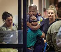 A Dallas Area Rapid Transit police officer receives comfort at Baylor University Hospital emergency room entrance on July 7, 2016, in Dallas.(Ting Shen/Staff Photographer )