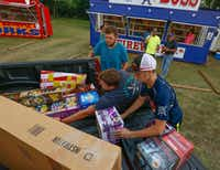 From left: Jeremiah Smith, Colton Taylor and Zane Taylor load up fireworks purchased by Cleve Magers (left background) and Tony Magers at Big Boss Fireworks along FM1187 near the western edge of Mansfield.(Ron Baselice/Staff Photographer)