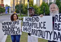 Sara Mokuria, co-founder of Mothers Against Police Brutality, holds a sign during an August memorial service for Bertrand S. Davis. His father, Otis Davis, stands in the middle with John Fullinwider, another co-founder of the anti-brutality group.  ((Ben Torres/Special Contributor))
