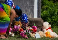 Adrian Moseley, of Dallas, plants a flower at a memorial as balloons and flowers wave in the wind at a home in the 2200 block of East Kiest Boulevard where a missing Lancaster teenager and a man were found dead Sunday.(Ryan Michalesko/Staff Photographer)