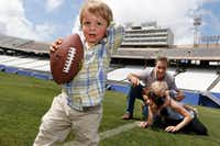Walker, not yet 2, and his sister, Marlowe, who turns 3 in September, are the only grandchildren of Dallas Cowboys great Don Meredith. Here, Walker plays football with his family. His father is Michael Meredith, an independent film director, screenwriter and producer and the only son of Don Meredith. Amit Nizan Meredith is Michael's wife and the mother of Walker and Marlowe. They were photographed at the Cotton Bowl in Fair Park in Dallas. (David Woo/<i>The Dallas Morning News</i>)