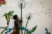 Essence Mahara poses for a photo against a backdrop of paintings of flora and fauna at Bishop and Melba streets in the Bishop Arts District. (Smiley N. Pool/Staff Photographer)