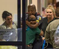DART police Sgt. Homer Hutchins (center) hugged DART Officer Shamika Sorrells in the hallway of Baylor's emergency room on the night of July 7. Nita Tarango, a social worker at Baylor (left), and Sherry Sutton, a nurse manager,  flanked the embrace.(Ting Shen/Staff Photographer)