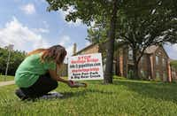 Diana Nowlin places fliers in the tube at a protest sign against a proposed traffic bridge in the middle of a wooded area in Grapevine.(Louis DeLuca/Staff Photographer)