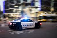 At 8:46 pm, 12 minutes before the shootings began exactly one year earlier, a Dallas Police cruiser races down Lamar Steet between Elm and Main on the anniversary of the attack which killed five police officers at the same location on Friday, July 7, 2017, in Dallas.(Smiley N. Pool/Staff Photographer)