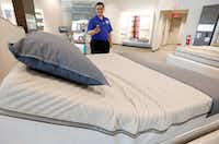 John Yelverton demonstrates the sleep technology that not only tracks your sleeping patterns, but works in concert with a number of features of the Sleep Number 360 Smart Bed. (Rogelio V. Solis/AP)