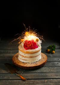 Local baker Kristen Massad's celebration cake, including a star sparkler, is called the Naked Vanilla Layer Cake, with strawberries, lemon curd and buttercream icing.(Tom Fox/Staff Photographer)