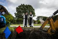 The Rev. Paul McCormick (left) and the Rev. Joseph Van House watch as workers prepare to remove the remains of two fellow Cistercian monks from their graves at Calvary Hill Cemetery in Dallas.(Smiley N. Pool/Staff Photographer)