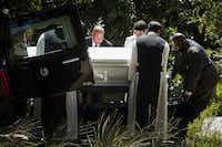 Monks assist funeral director Chris Taylor (facing, center) with the casket containing the remains of the Rev. Damian Szodenyi at Cistercian Abbey in Irving.(Smiley N. Pool/Staff Photographer)