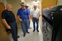 Capt. Jeff Modawell (from left) smiles after Patrick Travers, Kelly Walker and Benny Plunkett deliver a drink machine stocked with soft drinks in the hallway at Station 53 in Dallas. The East Dallas neighborhood raised money to buy the drink machine, which was on the firefighters' wish list of items they would like to have. (Jae S. Lee/Staff Photographer)