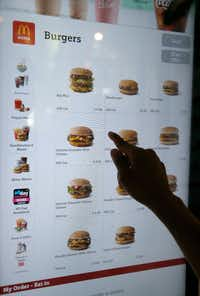 A customer orders food at a self-service kiosk at a McDonald's restaurant in Chicago. (AP/Charles Rex Arbogast)