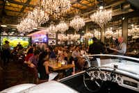 An 11-foot aquarium with a bright yellow ninesweeper, MG-A sports car and 63 chandeliers decorate the dining room at Town Hearth restaurant on Market Center Boulevard. (Ashley Landis/Staff Photographer)