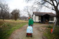 Demetrius X. Blair delivers cases of water from Mount Zion Baptist Church to a home down the street in Sandbranch.(Rose Baca/2016 File Photo)