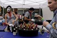 Robyn Pinilla, left, and David Pinilla, center, serve wine to Jeff Chesnut, right, during Bastille on Bishop on July 14, 2013 on Bishop Ave. in Dallas. (Sarah Hoffman/Staff Photographer)