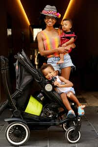 Kenya MomPremier of Dallas holds her son Kemet MomPremier, nine months old, while her other son Miken MomPremier, 2, sits in a stroller during a photograph in the alley connecting Commerce and Main streets on July 11. (Andy Jacobsohn/Staff Photographer)