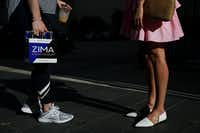 Caitlin Costa (left) and Olivia Simons, both of Dallas, speak along Commerce Street on July 7. Costa was carrying a limited release Zima to surprise her husband. (Andy Jacobsohn/Staff Photographer)