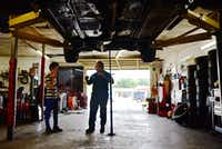 Joaquin Godinez chats with his son Cristian Godinez at his auto mechanic shop.(Ben Torres/Special to The Dallas Morning News)