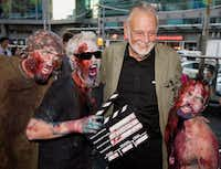 In this Sept. 12, 2009, file photo, director George Romero poses with some fans dressed as zombies after accepting a special award during the Toronto International Film Festival in Toronto.  (Darren Calabrese/The Canadian Press via AP, File)(Darren Calabrese/The Associated Press)