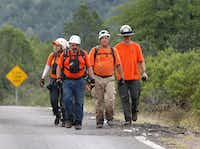 Members of the Tonto Rim Search and Rescue team walk back to the Gila County Sheriff's Office mobile command center after searching along the banks of the East Verde River in Payson, Ariz. (AP Photo/Ralph Freso)