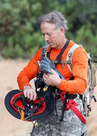 A member of the Tonto Rim Search and Rescue team gathers his gear during an operation along the banks of the East Verde River to find victims of a flash flood in Payson, Ariz. (AP Photo/Ralph Freso)