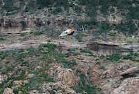 A helicopter flies above the rugged terrain along the banks of the East Verde River during a search and rescue operation for victims of a flash flood in Payson, Ariz. (AP Photo/Ralph Freso)