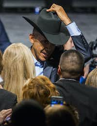 President Barack Obama tries on a cowboy hat from a member of the crowd after speaking at a Democratic National Committee event at Gilley's Club Dallas on March 12, 2016, in Dallas.(Ashley Landis/Staff Photographer)