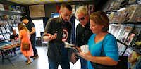 Donny Cates (center), an Austin-based comic book writer who grew up in Garland, shows his parents Rhonda and Chris Cates one of his comic books during a book signing at Red Pegasus Comics in the Bishop Arts area of Dallas, Wednesday, June 7, 2017. (Tom Fox/Staff Photographer)