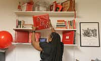 Amye Thompson Hollins, president of local chapter of Delta Sigma Theta Sorority, looks at one of the scrapbooks stored at the sorority house in Dallas.(Louis DeLuca/Staff Photographer)