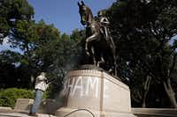 """Tino Banda, an employee of the City of Dallas Parks and Recreation Department, uses a power washer to remove the spray painted word """"SHAME"""" from a statue of General Robert E. Lee at Robert E. Lee Park.(Staff photo/FILE 2015/G.J. McCarthy)"""