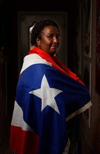 Sara Rosado, draped in a Puerto Rican flag, lives in Arlington. (Jae S. Lee/Staff Photographer)