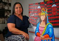 Artist Katherine Rodriguez, with one of her paintings at Sara Rosado's home in Arlington, left her home on the island territory 25 years ago. (Jae S. Lee/Staff Photographer)