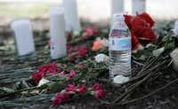 A bottle of water, flowers, candles, and stuffed animals help form a makeshift memorial in the parking lot of a Walmart store near the site where authorities Sunday discovered a tractor-trailer packed with immigrants outside a Walmart in San Antonio, Monday, July 24, 2017. Several people died and others hospitalized after being crammed into a sweltering tractor-trailer in the midsummer Texas heat, according to authorities in what they described as an immigrant-smuggling attempt gone wrong.(Eric Gay/AP)