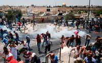 Palestinian worshippers ran for cover from tear gas fired by Israeli forces outside Jerusalem's Old City in front of the Al-Aqsa mosque compound on July 21, after Israeli police barred men under 50 from entering the Old City for Friday Muslim prayers as tensions rose and protests erupted over new security measures at the highly sensitive holy site.  The ban came after Israeli ministers decided not to order the removal of metal detectors erected at entrances to the Al-Aqsa mosque compound, known to Jews as the Temple Mount, following an attack nearby a week ago that killed two policemen.(Ahmad Gharabli/Agence France-Presse)