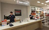 Rhett Biehahn (left) and Tami Doss work Penney's pickup counter for online purchases at the J.C. Penney store at Stonebriar Centre in Frisco. (Louis DeLuca/Staff Photographer)