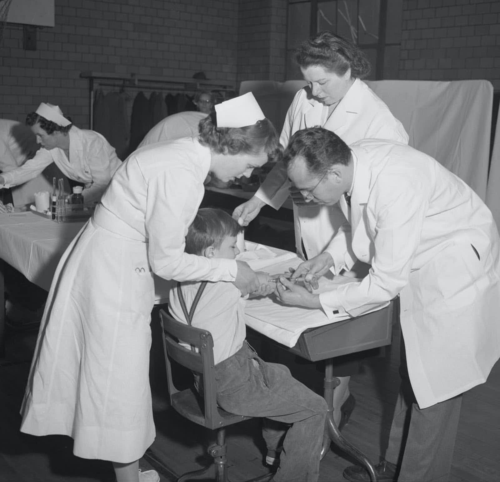 <p>Dr. Jonas Salk (right), the scientist who developed the first polio vaccine, administers an injection to a boy in Pittsburgh. The Salk vaccine came into use in 1955. The oral vaccine was developed by Dr. Albert Sabin and was used on the public starting in 1961. (File Photo/The Associated Press)</p>