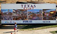 A Texas Rangers fan passes the Texas Live! entertainment complex under construction near Globe Life Park and AT&T Stadium in Arlington.(Tom Fox/Staff Photographer)