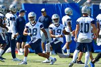 Dallas Cowboys wide receivers Brian Brown (18) and Brice Butler (19) and teammates warm up during NFL football training camp in Oxnard, Calif., Tuesday, July 25, 2017.(Gus Ruelas/AP)