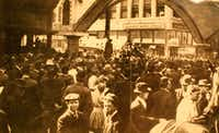 Close-up view of a postcard that depicts a public lynching in Dallas. In this photo, taken on March 3, 1910, a vast mob of 10,000, many of them children, stand shoulder to shoulder around Allen Brooks, a black man. He is lynched from a telephone pole at Elm and Akard streets in downtown Dallas. ( )