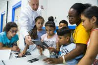 CEO Dave Woodyard (second from left), helps third graders with a 4D dinosaur tablet activity during a Catholic Charities of Dallas summer camp on Monday, July 10, 2017.(Ashley Landis/Staff Photographer)