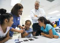 Educational programs manager Ana Maria Schaller, second from left, and CEO Dave Woodyard, second from right, help third graders Dairene Fernandez, 8, left, Rocelynne Rangel, 8, center, and Sophia Tolentino, 8, right, with a 4D dinosaur activity.(Ashley Landis/Staff Photographer)