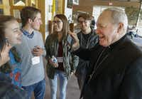 From left: Xavier Diaz, Elizabeth Holman, Robert Le Grand, Michelle Hodgson and Michael Williams laugh with Bishop Edward Burns as he shows a photo of his mom while visiting with the crowd after Friday morning's session of Feedback for Francis.(Ron Baselice/Staff Photographer)
