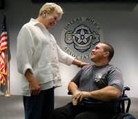 DART Detective Justin Ellis is greeted by Maurine Dickey, founder and chairwoman of Barbecue, Boots & Badges, at the Dallas Police Association office in Dallas on Monday.(David Woo/Staff Photographer)