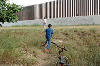 A boy runs toward a section of U.S. border fence from his backyard in the South Texas town San Benito.  (Miguel Roberts/The Associated Press)