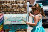 Aviana Ragan, 4, places a letter in a handmade mailbox in honor of her younger sister.(Ashley Landis/Staff Photographer)
