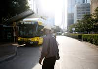 Joshua Miller crosses the street to a bus facility. He spends much of his day traveling on buses and trains to  appointments.(Tailyr Irvine/The Dallas Morning News)