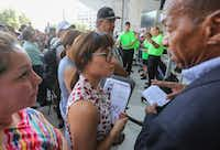 Ariana Paz (center), a new developer, talked with community activist Anthony Bond (right) after she bought a house in a public auction in downtown Dallas on Tuesday that Bond was trying to save for the family that's living in it. Paz bought the Palmas' home for $37,000.(Ron Baselice/Staff Photographer)