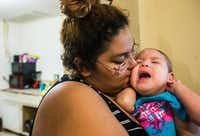 Alexandra Maldonado, 18, kissed her daughter, Delilah Palma, 1, who suffers from a condition called encephalocele, in their dining room on Monday. A developer, Ariana Taz, bought the Palmas' home at public auction on Tuesday. Now, the Palmas are unsure of where they will go if the developer won't let them stay as renters.(Ashley Landis/Staff Photographer)