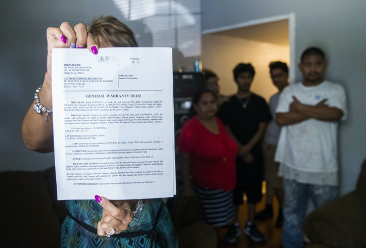Realtor Lisette Caraballo, left, holds up a false deed to the Palma  family's home on Pine Street in South Dallas Monday. The legal owner had  filed for ...