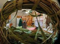 A wreath made of cattail reeds frames Mike Turrentine as he reweaves a child's rocking chair in the kitchen of his Garland home.(Ron Baselice/Staff Photographer)